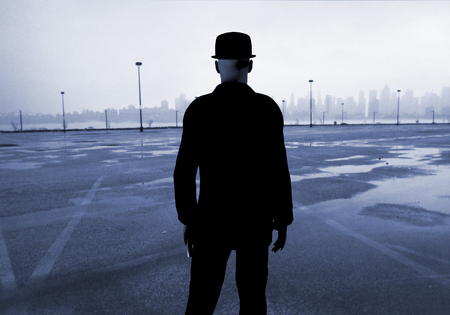 Man in classic black suit stands on empty parking lot. Modern city at the horizon