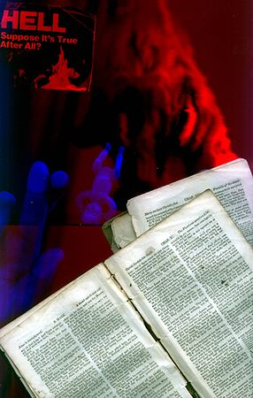 Hell Awaits. Demon and pages of Holy Bible Stock Photo