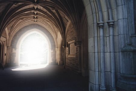 Gothic archway with light illuminating the path.