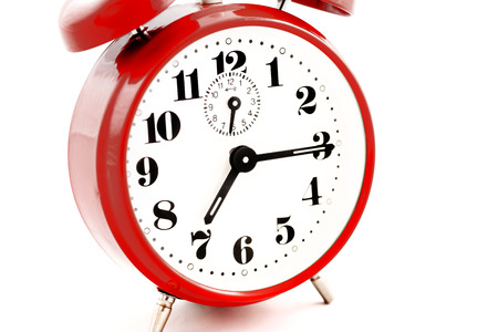 Round red alarm clock on white background isolated. The image of the retro clock shows a quarter past seven.