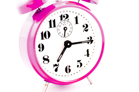 Round pink alarm clock on white background isolated. The image of the retro clock shows a quarter past seven. Stock Photo