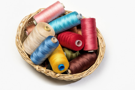 Still life of colorful spools of thread in a little basket on a white background - Closeup Detail - concept fashion DIY do it yourself clothing sewing fun creativity Stock Photo
