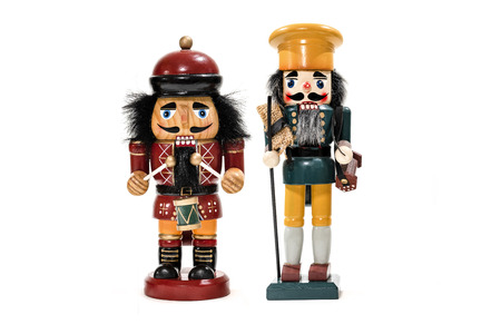 Merry Christmas: Two traditional colorful vintage wooden nutcracker puppets in uniform isolated on white background and copyspace for text - concept tradition festive Christmas decoration ornament