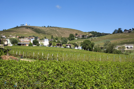 France, Crus des Beaujolais, Fleurie: Vineyard and French small town with old chapel (Chapelle de la Madone) on top of a hill and blue sky in the background - concept travel vacation pilgrimage