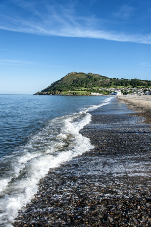 Ireland, County Wicklow, Bray: Shoreline of Irish spa seaside resort Bray with waves, Bray Head and blue sky in the background. Stock Photo