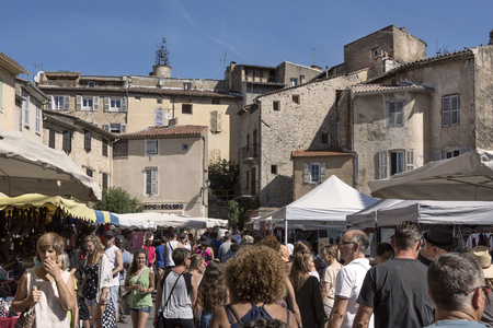 France, Provence, Lorgues: People residents tourists men women at regular weekly market with panoramic skyline of the old medieval French village and blue sky in the background. August 15, 2017