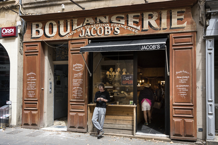 France, Provence, Aix-en-Provence: Street scene with people men women in front of an old vintage traditional bakery (Boulangerie) in the city center of the famous French town. August 11, 2017