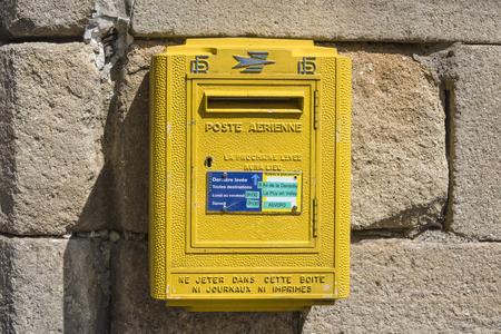 Francia, Provenza: Cassetta postale in metallo giallo francese su una parete esterna - concetto di posta comunicazione postale storico messaggio nazionale lettera consegna pacchi business letterbox simbolo. 07 agosto 2017