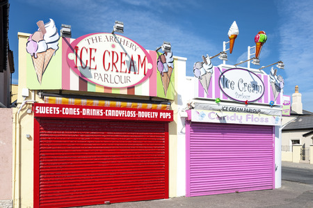 Ireland, County Wicklow, Bray: Two colorful closed ice cream parlors with red and pink shutters with blue sky in the background. June 06, 2015