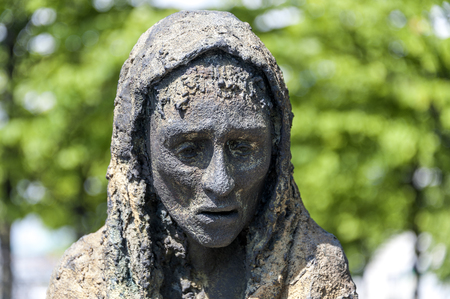 Ireland, Dublin: Famous Famine Memorial in the city center of the Irish capital - detail of woman's head with green trees in the background. June 09, 2015