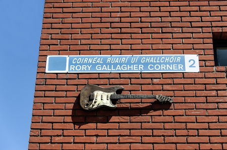 Ireland, Dublin: Street scene with replica of musician Rory Gallaghers guitar on a brick wall in the famous Temple Bar district of the Irish capital with blue sky in the background. June 09, 2015