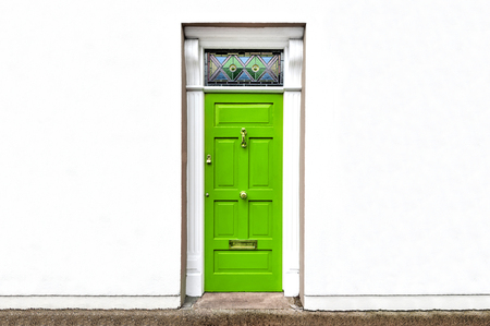Green door closed with old style golden door handle, mailbox slot and white exterior wall facade isolated on white background with copyspace - concept doorway home design entrance exit style vintage Stock Photo