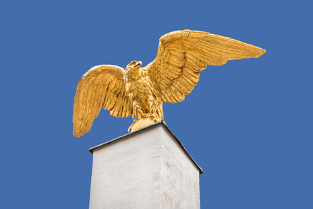 Golden eagle statue sculpture with spread wings on pedestal from below isolated against blue background - concept victory majectic monument beautiful dynamic royal air force military freedom kingly
