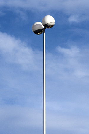 High tall lamp post streetlight with futuristic two spherical round light fixture on the upper end with blue sky and white clouds in the background - concept lantern illumination modern design future street city town