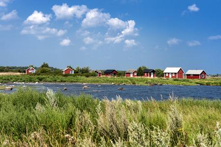 Svezia, Oland: Vista panoramica con scena costiera all'aperto, vecchie case di legno tradizionali rosse sull'isola svedese Oeland - concetto di paesaggio panoramico natura vacanza per il tempo libero Archivio Fotografico