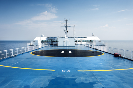 Helicopter landing site helipad helideck of a big ship boat tanker with captains bridge in the background - concept passenger transport sea travel copter flight maritime aviation nautical nautics