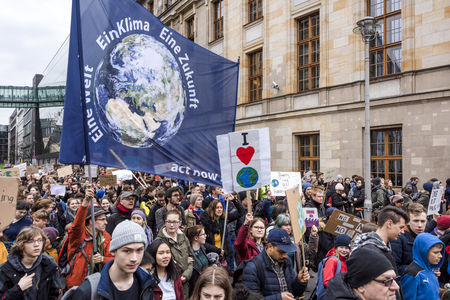 Germany, Berlin: Young pupils people students men women with big 'One world, one climare, one future' flag at Fridays for Future demonstration in the city center of the German capital. March 29, 2019