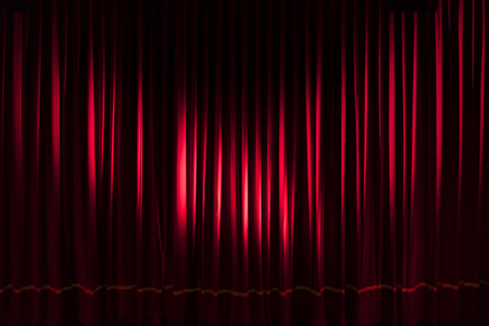 Heavy red curtain illuminated by two spotlights - concept theater show entertainment performance background