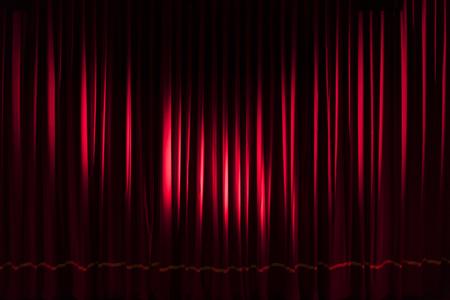 Tenda rossa pesante illuminata da due faretti - sfondo di performance di intrattenimento di spettacolo teatrale di concetto