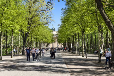 Germany, Berlin, Tiergarten: People residents tourists visitors in public park with famous Brandenburg Gate in the city center of the German capital with blue sky in the background. April 21, 2018