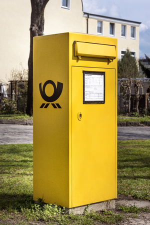 Germany, Berlin: Street scene with typical yellow metal mailbox of German company Deutsche Post which stands upright on the grass in the German capital. April 09, 2016