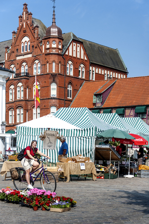 Sweden, Ystad: Market scene of regular weekly market with people, woman, man, merchant, cyclist, market stalls, flowers, brick building and blue sunny sky in the background. July 28, 2014 新聞圖片