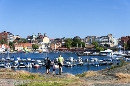 Sweden, Karlskrona, Stakholmen: Panoramic view of Swedish town with young family, central marina, water, boats, pier and buildings at Baltic Sea. July 07, 2014