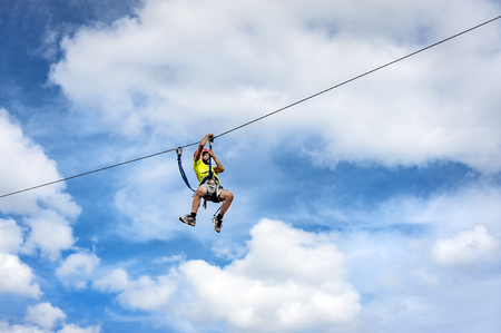Sweden, Torpoens: Young boy on an outdoor steel cable slides down to a plattform - concept leisure activity fun adventure sports lifestyle free young vacation risk danger travel. August 10, 2014