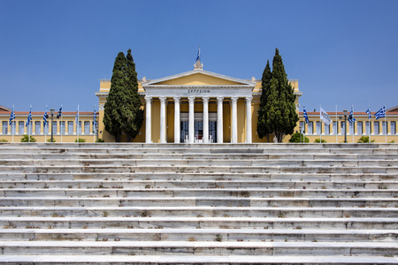 Greece, Athens: Front view of famous Zappeion building in the city center of the Greek capital and part of National Gardens with stairs, green trees and blue sky in the background. April 29, 2018