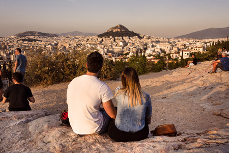 Greece, Athens, Lycabettos: Sunset panorama view of famous Mount Lycabettus in the city center of the Greek capital with people young couple woman man skyline horizon and blue sky. April 25, 2018
