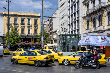 Greece, Athens, Omonia square: Street scene in the city center of the Greek capital with cars, yellow cabs, busy traffic, people, residents, shops, buildings and blue sky in background. April 26, 2018