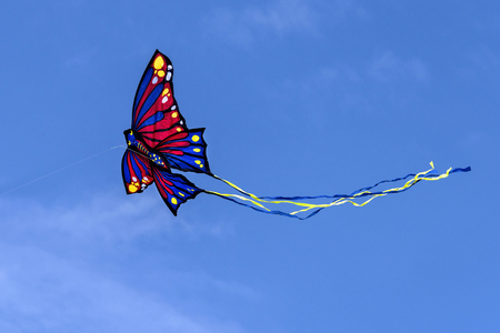 Colorful red yellow butterfly shaped kite with long tail flying in the blue sky among the clouds - concept leisure lifestyle fun game play season freedom object wallpaper isolated against background