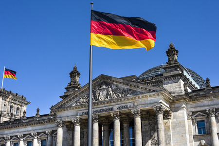 Germany, Berlin: Two national flags and famous part of main entrance portal of parliament building Deutscher Bundestag (former Reichstag) in the city center of the German capital with blue sky.