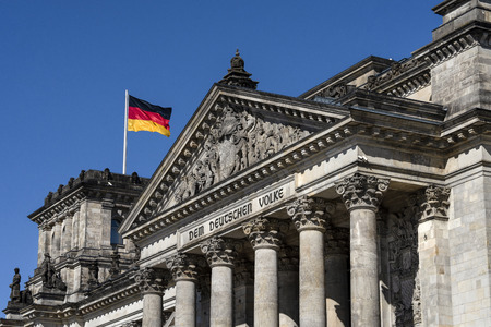 Germany, Berlin: Colorful national flag and famous part of main entrance portal of parliament building Deutscher Bundestag (former Reichstag) in the city center of the German capital with blue sky. 版權商用圖片