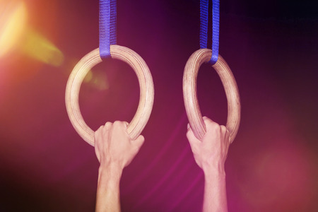Sports, gymnastics: Two male hands grab traditional wooden gymnastic rings tightly in a gym isolated on black background against light - concept athletics olympics olympic games strength activity