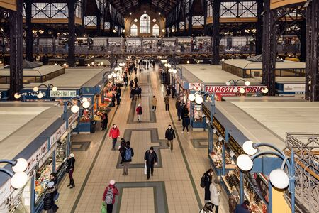 Hungary, Budapest: Panorama inside view of famous indoor Great Market Hall or Central Market Hall in the city center of the Hungarian capital with people men women tourists - business. Feb 05, 2019