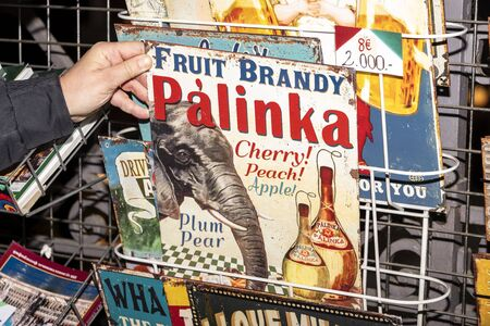 Hungary, Budapest, Great Market Hall: Hand holds an old retro colorful metal plate of traditional fruit brandy Palinka brand - concept vintage tradition beverage alcohol drink souvenir. Feb 05, 2019 에디토리얼
