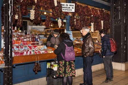 Hungary, Budapest: People men women at fruit and vegetables stall inside famous indoor Great Market Hall or Central Market Hall in the city of the Hungarian capital - concept business. Feb 05, 2019