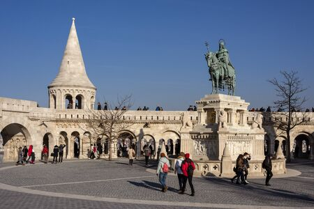 Hungary, Budapest, Castle Hill, Fischerbastei: People visit statue of St Stephen I at famous Fishermans Bastion near Matthias Church above the city center of the Hungarian capital. Feb 06, 2019
