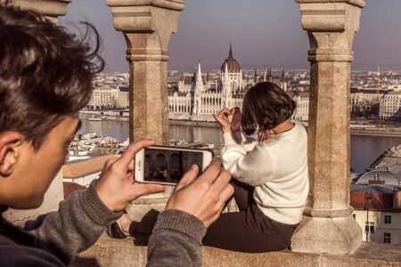 Hungary, Budapest, Castle Hill, Fischerbastei: Young couple takes photos at famous Fishermans Bastion with Donau Danube river to Hungarian Parliament in the city center of the capital. Feb 06, 2019 에디토리얼