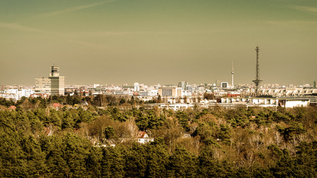 Germany, Berlin, Teufelsberg: Panorama skyline view of the city center of the German capital from above with famous tv tower, Radio Tower (Funkturm) and green park trees in foreground. Stock Photo