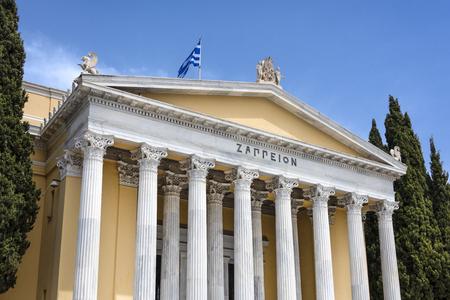 Griechenland, Athen: Vorderansicht des berühmten Zappeion-Gebäudes im Stadtzentrum der griechischen Hauptstadt und Teil der Nationalgärten mit blauem Himmel im Hintergrund - Konzeptarchitektur Reisegeschichte Standard-Bild