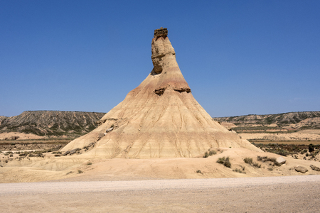 Spain, Bardenas Reales: Famous touristic hot spot called Castil de Tierra in the Spanish natural semi desert sierra national park with rocky mountain chain, wide plains and blue sky in the background. Stok Fotoğraf