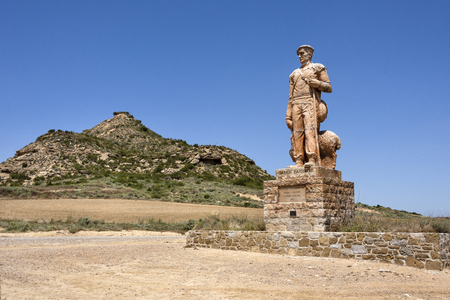 Spain, Bardenas Reales: Statue in rememberance of Pastor Bardenero at one entrance of the famous natural semi desert sierra with rocky mountain chain, wide plains and blue sky in the background.