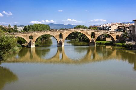 """Hiszpania, Puente La Reina, Gares: Panorama słynnego romańskiego mostu nad rzeką Arga z panoramą hiszpańskiego miasteczka dosłownie zwanego """"Mostem Królowej"""", zielonym brzegiem rzeki i błękitnym niebem."""
