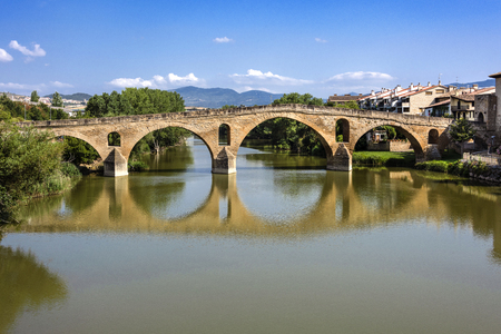 Spain, Puente La Reina, Gares: Panorama view of famous romanesque bridge over river Arga with skyline of Spanish small town literally named 'Bridge of the Queen', green riverside and blue sky.