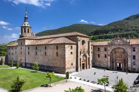 Spain, La Rioja, San Millan de la Cogolla: Panoramic view of famous Monastery of San Millan de Yuso with public park, hills and blue sky. It's the birthplace of modern written spoken Spanish language. Archivio Fotografico