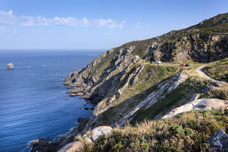 Spain, Finisterre: Panorama of coastline with travellers campers on a natural camping site, rocky cliff, ocean water,  lue sky. The place was famous for being the end of the world - concept travel