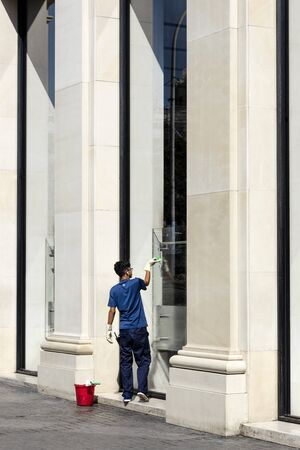 Spain, Barcelona: Young male window cleaner washer opposite the famous Catalonia Square (Placa de Catalunya) cleans big windows in the city center of the Spanish town with blue sky. July 01, 2018