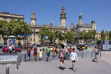 Spain, Barcelona, near harbor: Daily street scene at Passeig de Colom crossing in the city center of the Spanish town with old post office, people, tourists, men, women and blue sky. July 01, 2018